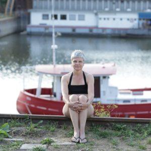 Foto von einer brustlosen Frau im Bikini vor einem Boot